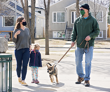 Julie and her daughter chat and walk with a neighbour and his dog