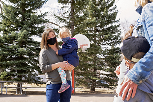 Julie holds her daughter while chatting with another parent at the park.